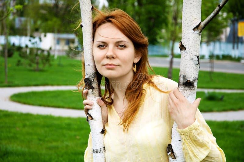 Een jonge vrouw dichtbij de boom stock fotografie