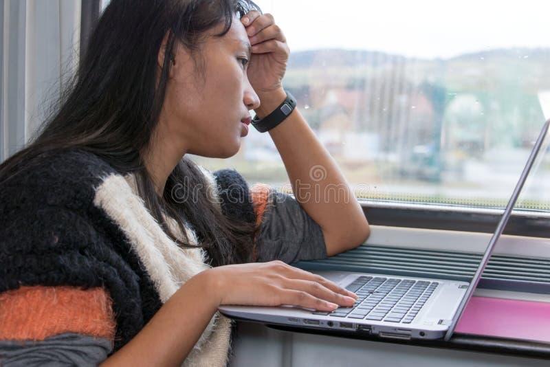 Een jonge vrouw die aan een computer op een trein werken stock foto
