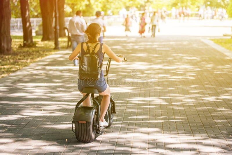 Een jonge vrouw die de emissieloze fiets van de eco elektrische autoped in een stadspark berijden stock foto