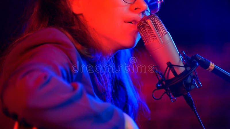 Een jonge vrouw die door mic in T.L.-verlichting in de studio zingen royalty-vrije stock fotografie