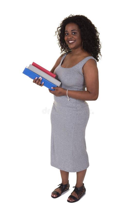 Een jonge vrouw die een stapel boeken houden stock foto's