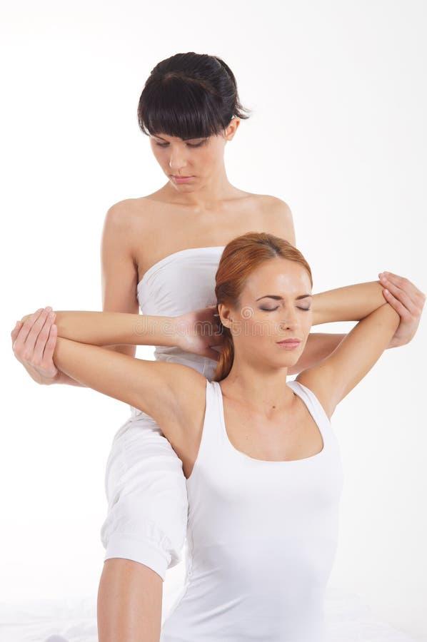 Een jonge vrouw die een traditionele Thaise massage krijgen stock fotografie