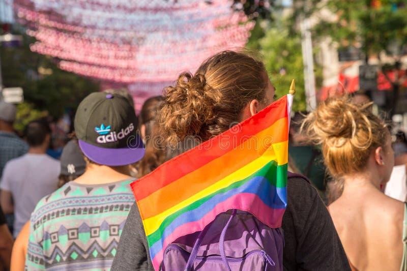 Een jonge vrouw die een vrolijke regenboogvlag houden royalty-vrije stock foto's