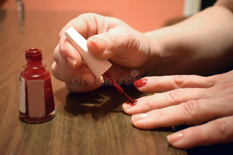 Een jonge vrouw die haar die spijkers krijgen tijdens een manicure worden geschilderd royalty-vrije stock afbeeldingen