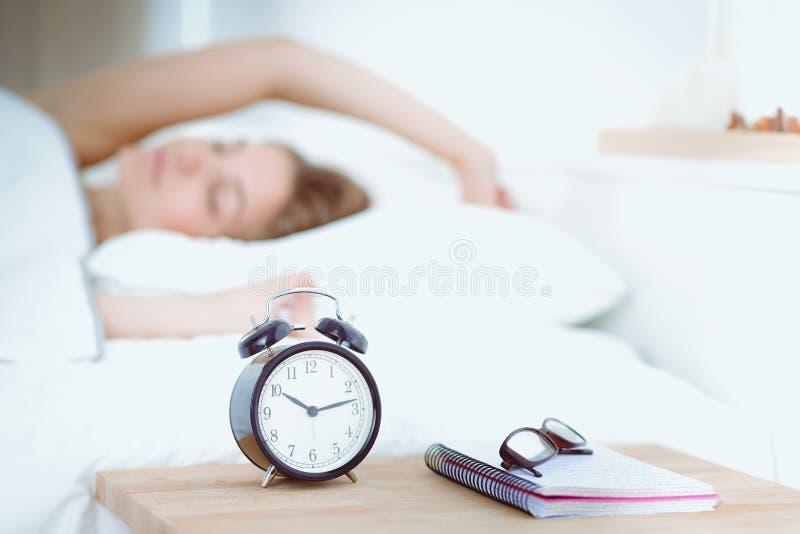 Een jonge vrouw die haar wekker in de ochtend uitstelt royalty-vrije stock afbeeldingen