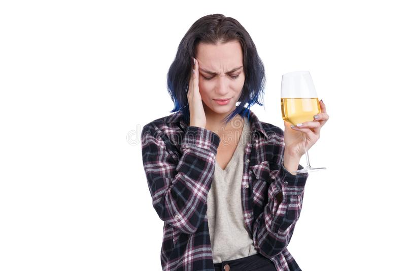 Een jonge vrouw die, die een hoofdpijn tonen, en een glas wijn in haar hand houden Geïsoleerd op wit royalty-vrije stock afbeeldingen