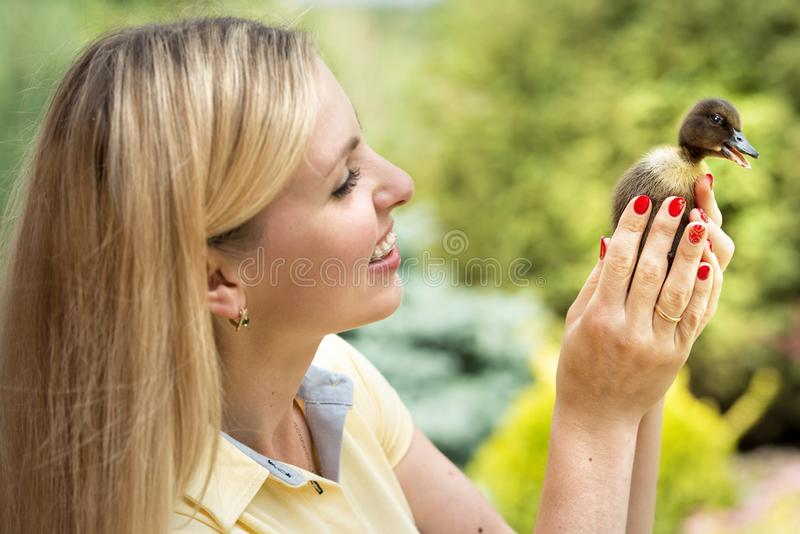 Een jonge vrouw, die een klein eendje houden royalty-vrije stock afbeeldingen