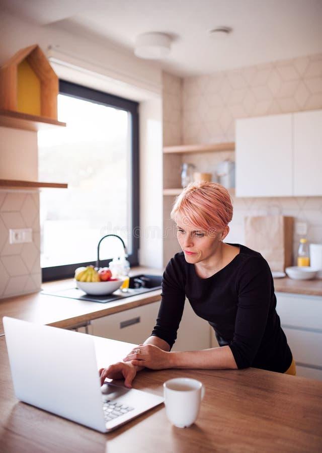 Een jonge vrouw die laptop in een keuken thuis met behulp van stock afbeelding