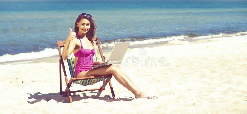 Een jonge vrouw die met laptop op een mooi strand ontspannen stock foto's