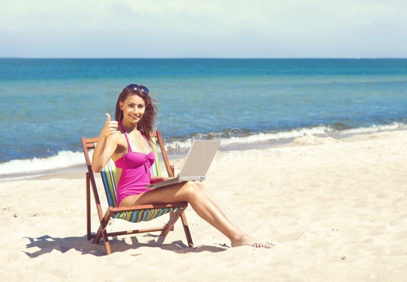 Een jonge vrouw die met laptop op een mooi strand ontspannen stock fotografie