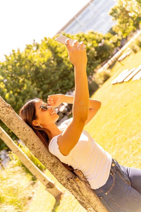 Een jonge vrouw die naast een boom staat en een selfie neemt stock foto