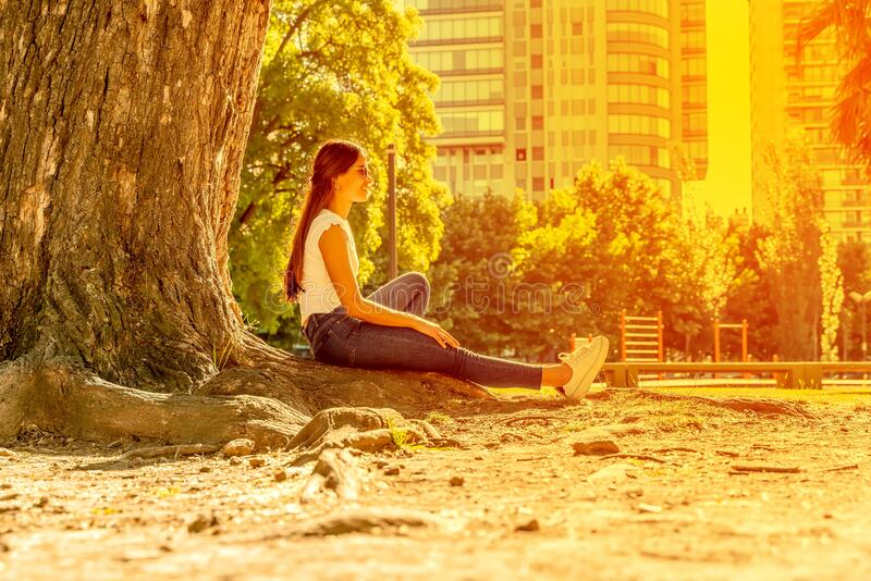 Een jonge vrouw die naast een boom zit en geniet van de zonneschijn royalty-vrije stock fotografie