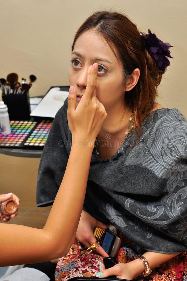 Een jonge vrouw die op haar wordt toegepast maakt omhoog door schoonheidsspecialist stock foto's