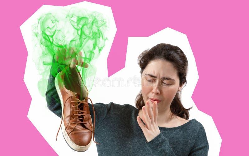 Een jonge vrouw die een tennisschoen in haar hand houden, die sterk stinkt Het concept de reclame van binnenzolen voor schoenen R stock fotografie