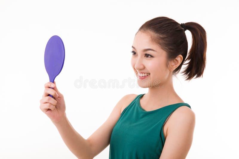 Een jonge vrouw die zich in een handspiegel bekijken stock foto