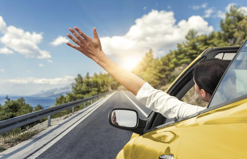 Een jonge vrouw drijft door auto aan het overzees en golft haar hand van een gele convertibele auto Vakantie op de overzeese kust stock afbeelding