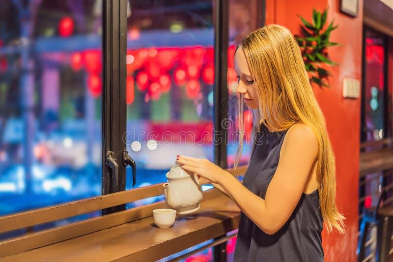 Een jonge vrouw drinkt Chinese thee op een achtergrond van rode Chinese lantaarns ter ere van het Chinese Nieuwjaar royalty-vrije stock afbeelding