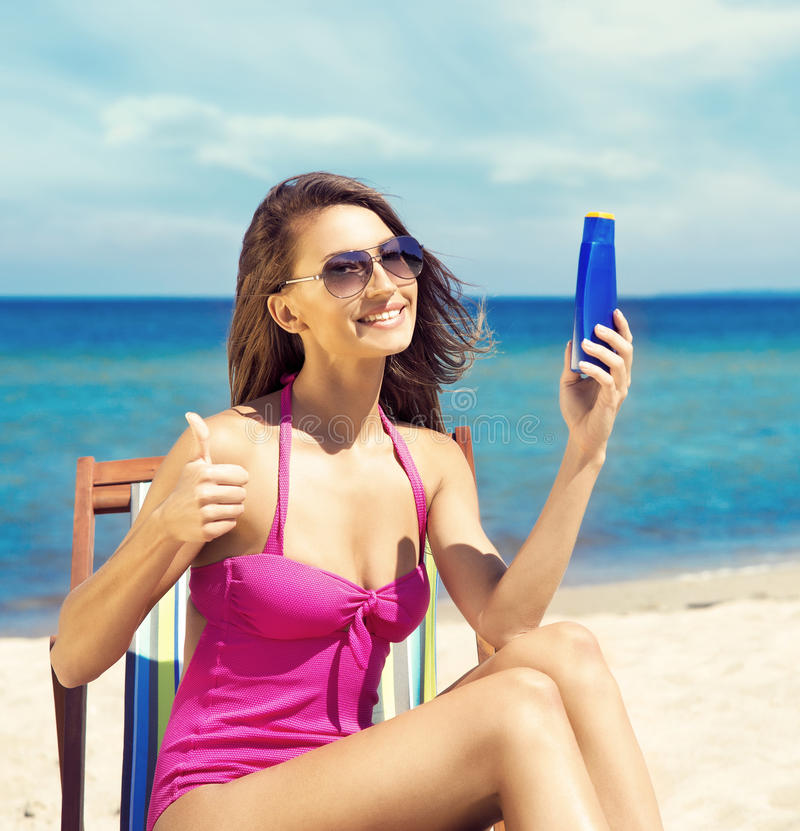 Een jonge vrouw in een zwempak die bruine kleur op het strand toevoegen royalty-vrije stock afbeelding