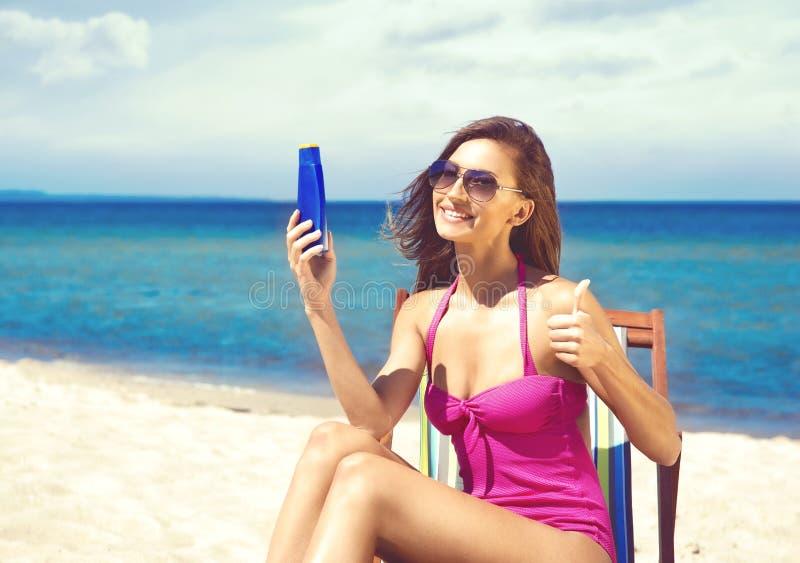 Een jonge vrouw in een zwempak die bruine kleur op het strand toevoegen stock fotografie