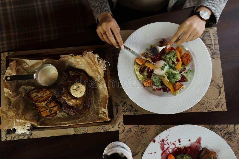 Een jonge vrouw eet een verse salade met zalm en een sappig lapje vlees en boter bij een elegant gelegde lijst in een restaurant royalty-vrije stock afbeelding