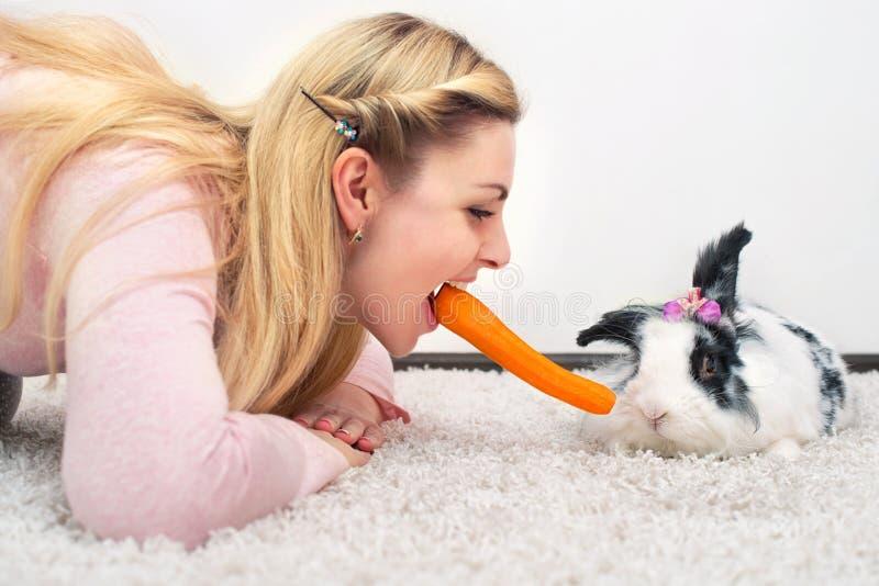 Een jonge vrouw en haar weinig geliefd konijn eten samen wortelen royalty-vrije stock foto's
