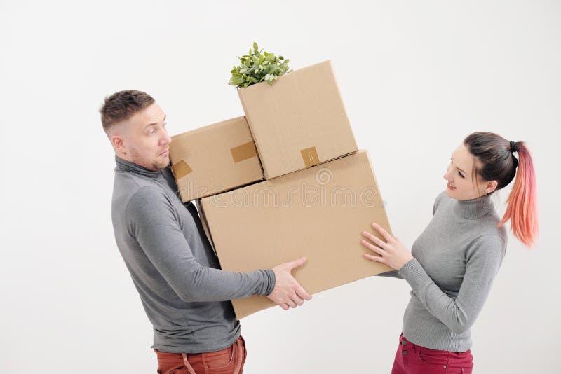 Een jonge vrouw en een man dragen zware kartondozen met dingen Witte lichte flat Zij lachen en kussen royalty-vrije stock afbeelding