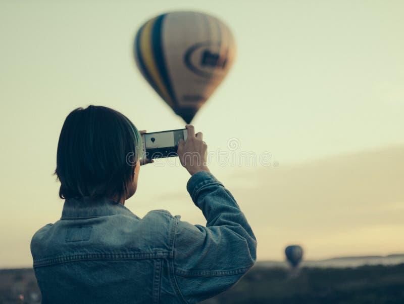 Een jonge vrouw fotografeert een ballonvlucht stock fotografie