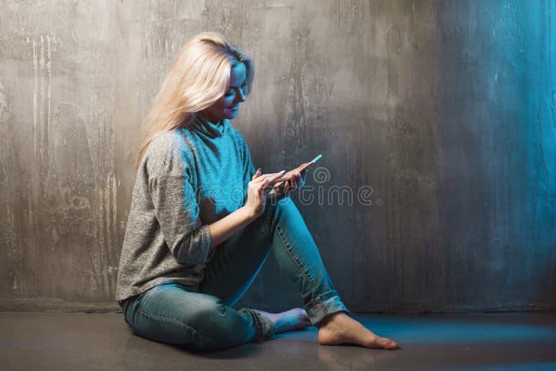 Een jonge vrouw gebruikt een smartphone, het blauwe stemmen stock afbeelding