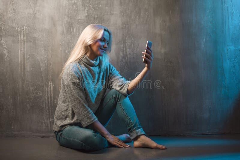 Een jonge vrouw gebruikt een smartphone, het blauwe stemmen royalty-vrije stock foto