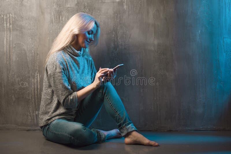Een jonge vrouw gebruikt een smartphone, het blauwe stemmen royalty-vrije stock fotografie