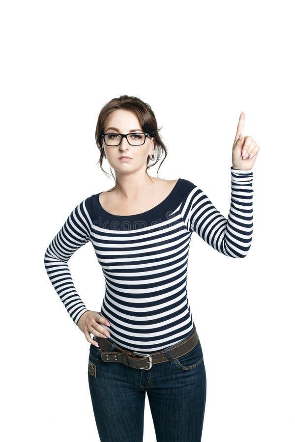 Een jonge vrouw in een gestreepte strakke blouse en ronde glazen toont een gebaar juist wapen opgeheven een vinger en kijkt strik stock afbeelding