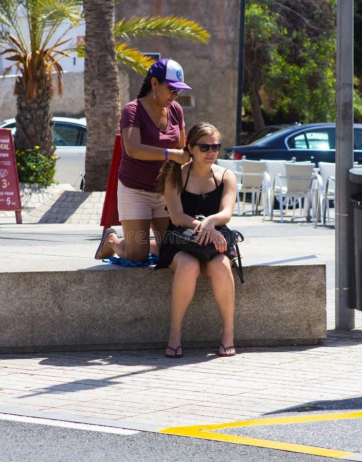 Een jonge vrouw heeft haar die haar door een lokale straathandelaar wordt gevlecht en wordt gevlecht in Playa Las Amerika in de C royalty-vrije stock fotografie
