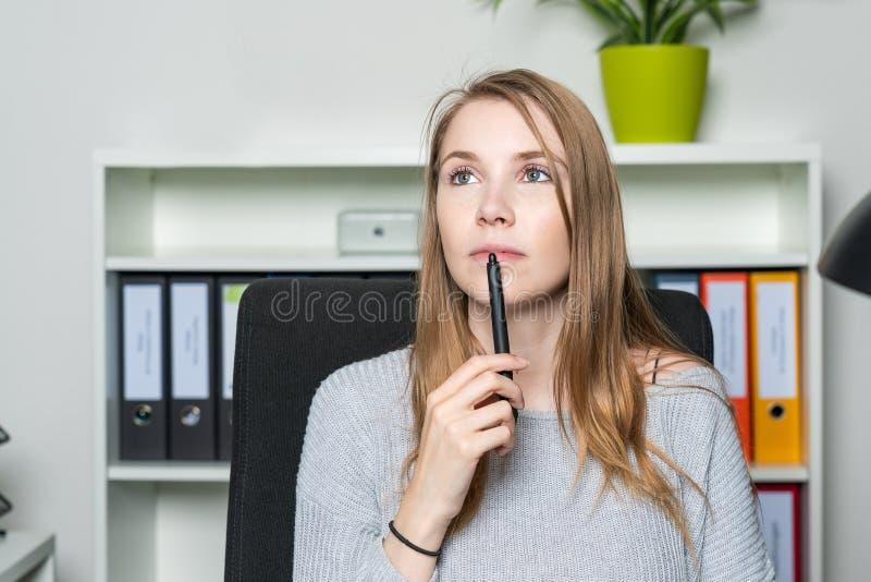 Een jonge vrouw in het bureau heeft een inspiratie stock afbeelding