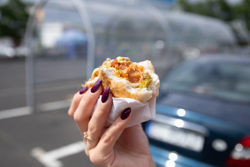 Een jonge vrouw houdt een gebeten hotdog royalty-vrije stock foto's