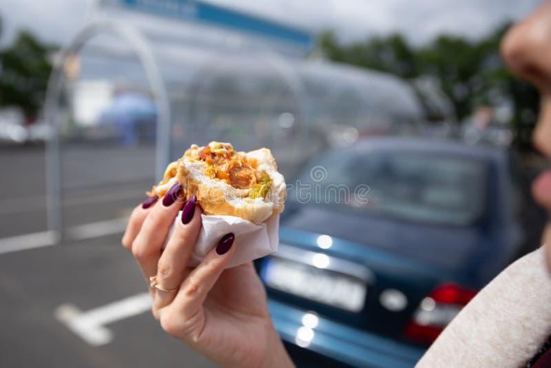 Een jonge vrouw houdt een gebeten hotdog royalty-vrije stock foto