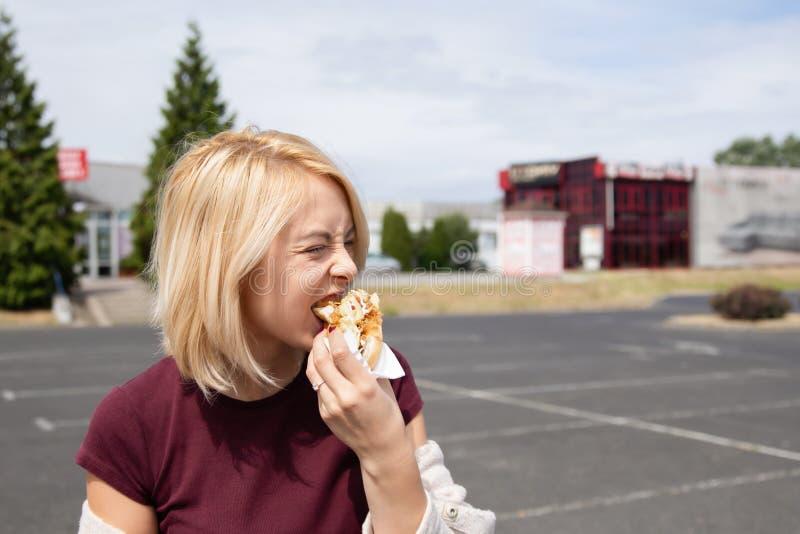 Een jonge vrouw houdt een gebeten hotdog royalty-vrije stock afbeeldingen