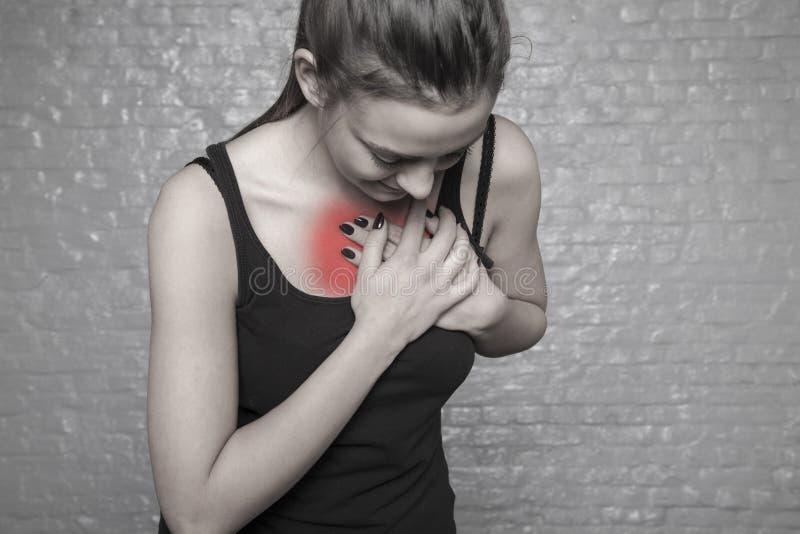 Een jonge vrouw houdt haar borst Mogelijke hartaanval stock fotografie