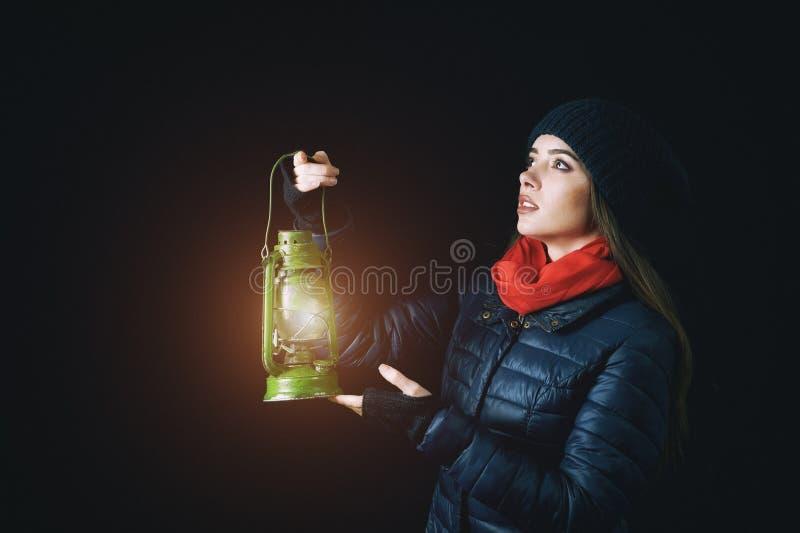 Een jonge vrouw houdt een kerosinelamp in de handen royalty-vrije stock foto's