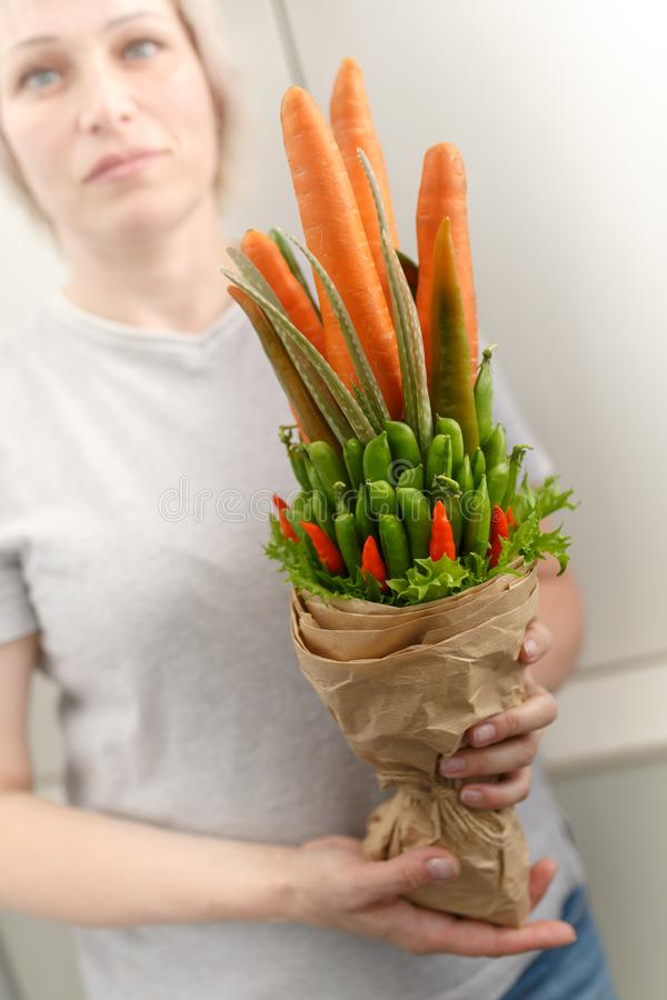 Een jonge vrouw houdt een plantaardig boeket bestaand uit wortelen, peulen, saladebladeren, Spaanse peper en aloë als symbool van stock afbeelding