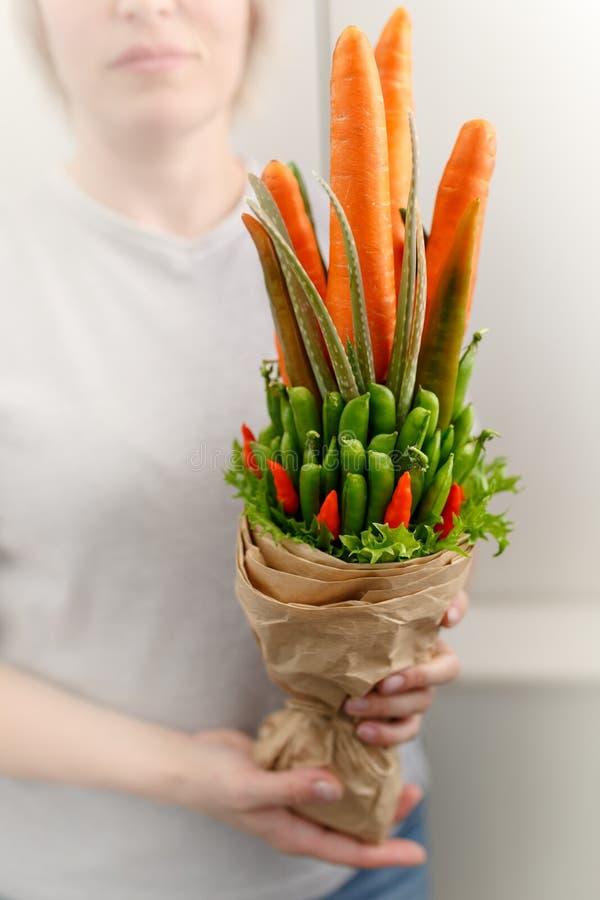Een jonge vrouw houdt een plantaardig boeket bestaand uit wortelen, peulen, slabladeren, Spaanse peper en aloë als gift aan een v royalty-vrije stock afbeelding
