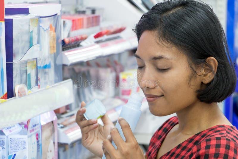 Een jonge vrouw kiest schoonheidsmiddelen bij een opslag stock foto
