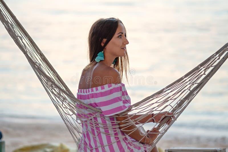 Een jonge vrouw kijkt aan de kant, zittend in een hangmat op het strand royalty-vrije stock foto's