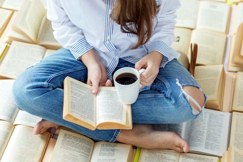 Een jonge vrouw leest een boek en drinkt koffie Concept voor de Dag van het Wereldboek, levensstijl, studie, onderwijs royalty-vrije stock afbeeldingen