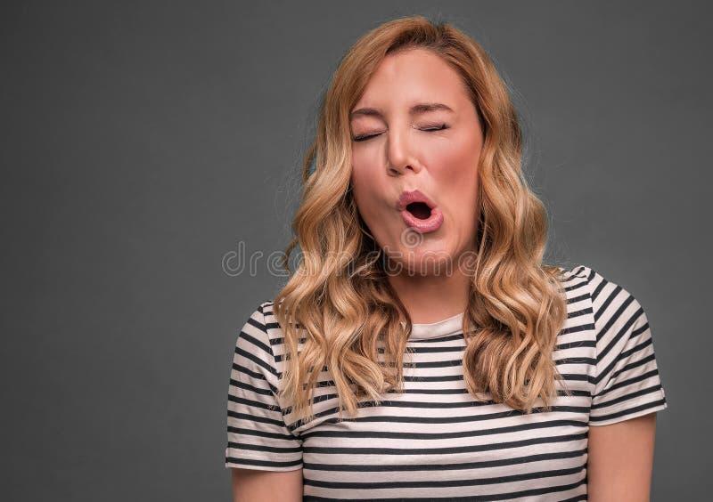 Een jonge vrouw is loensend een zuur grimas terwijl status tegen grijze achtergrond stock fotografie