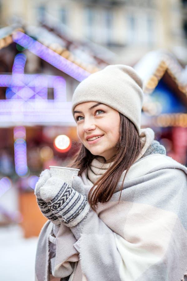 Een jonge vrouw loopt bij de Kerstmismarkt r stock fotografie