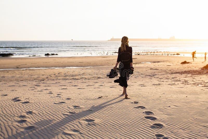 Een jonge vrouw loopt langs het zandige strand van de oceaan bij zonsondergang gang stock foto's