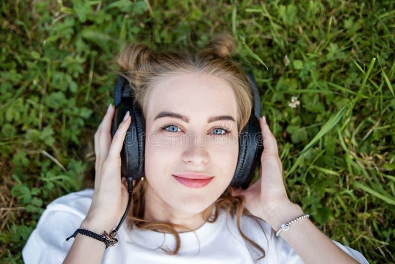 Een jonge vrouw luistert aan een audiobook met hoofdtelefoons Concept levensstijl, muziek stock foto's