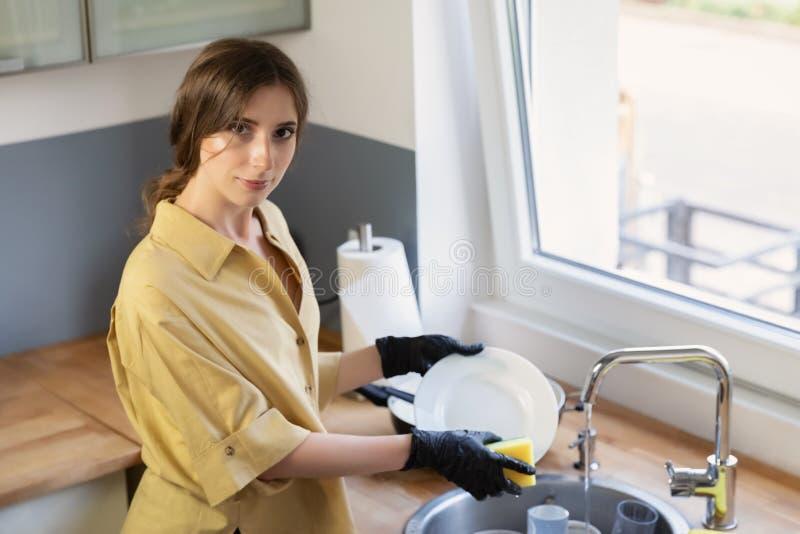 Een jonge vrouw maakt in de keuken schoon, die schotels wassen stock afbeeldingen