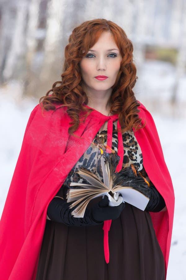 Een jonge vrouw met boek het branden stock afbeelding