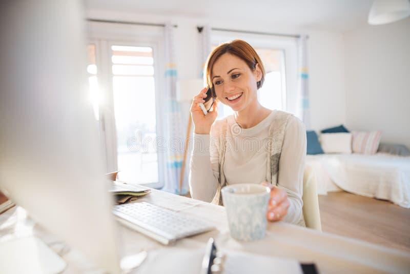 Een jonge vrouw met computer en smartphone die binnen, in een huisbureau werken royalty-vrije stock afbeeldingen